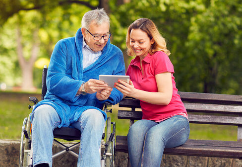 senior and caregiver looking on tablet device