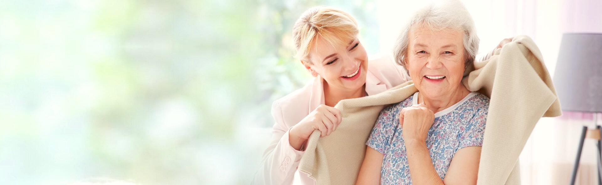 caregiver putting a blanket to a senior