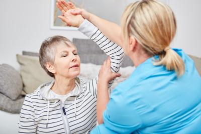 caregiver raising the shoulder of the senior