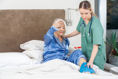 nurse giving care to a senior woman on bed