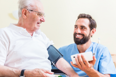 nurse checking blood pressure of a senior using new technology